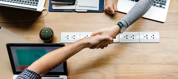 Sich schüttelnde Hände über einem Schreibtisch mit Laptops, Foto: rawpixel/unsplash