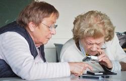 zwei ältere Frauen schauen durch eine Lupe auf ein Smartphone Foto: J. Skvorc